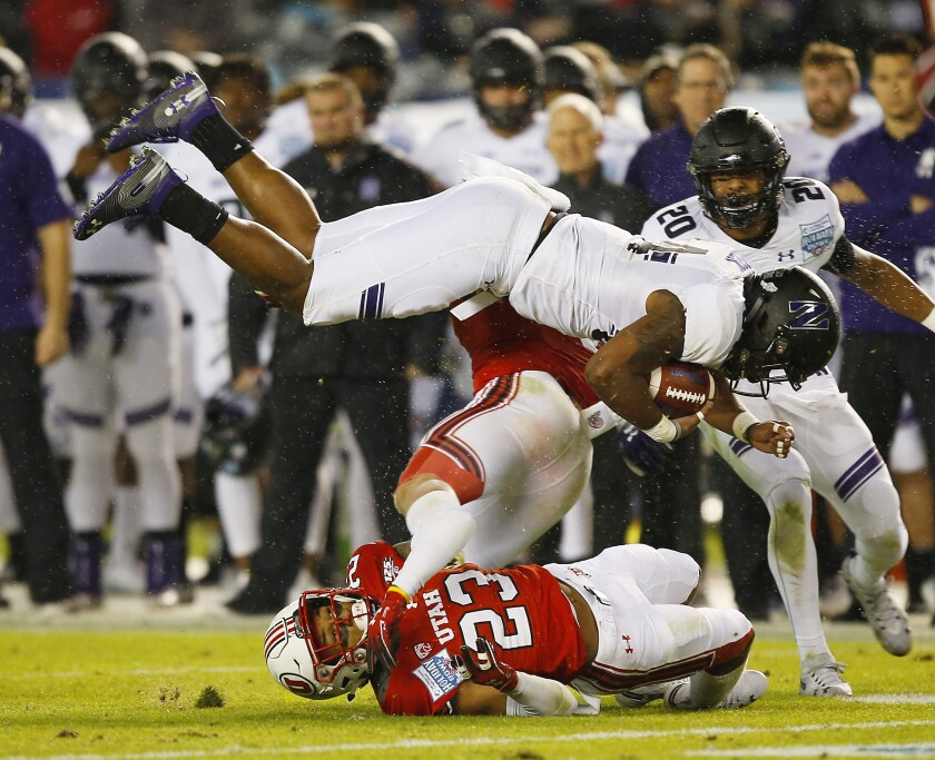 Northwestern's Cameron Green is upended by Utah defenders during last year's SDCCU Holiday Bowl.