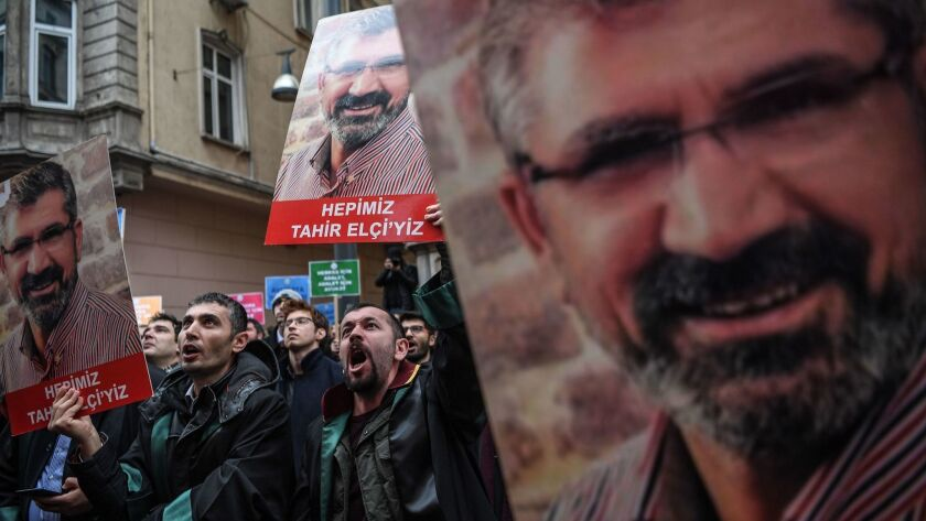 Demonstrators hold portraits of Tahir Elci, a slain human rights lawyer, during a Jan. 24, 2019, protest in Istanbul, Turkey. The 2015 shooting was filmed, but no arrests were made.