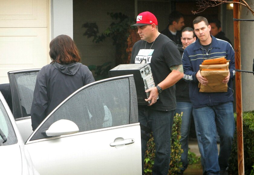 FBI and Homeland Security investigators carry a computer tower and manila envelopes from the Corona, Calif.,  home of Syed Raheel Farook while executing a search warrant at the home on Thursday, Feb. 18, 2016. FBI agents on Thursday were searching the California townhome of the brother of one of th