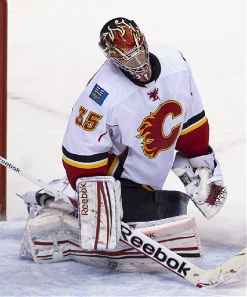 Calgary Flames goalie Henrik Karlsson (35) reacts after Vancouver Canucks Andrew Ebbett's game winning overtime goal went past him during NHL hockey action at Rogers Arena in Vancouver, British Columbia, Saturday, March, 31, 2012.  (AP Photo/The Canadian Press, Jonathan Hayward)