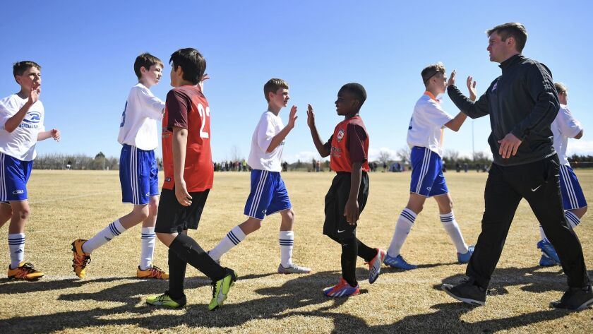 Mtabi Makeci Ebuela, 12, center, and his team shakes hands with opponents after a soccer game in Gre