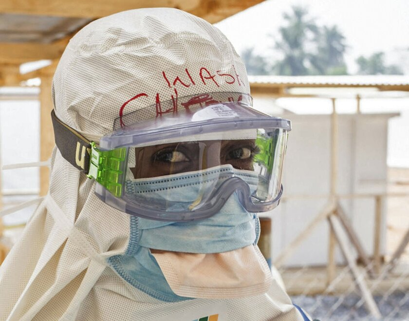 FILE - In this file photo taken on Monday, March 2, 2015, a health care worker wearing virus protective gear before entering a high risk zone at an Ebola virus clinic operated by the International Medical Corps in Makeni, Sierra Leone. Despite the drop in reported Ebola cases, Dr. Bruce Aylward, leading WHO's Ebola response, declared Friday April 10, 2015, that it's too early for World Health Organization to downgrade the global emergency status of the biggest-ever Ebola outbreak in Africa. (AP Photo/ Michael Duff, FILE)