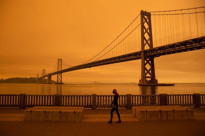A woman walks along The Embarcadero under an orange smoke-filled sky in San Francisco, California on Sept. 9, 2020.