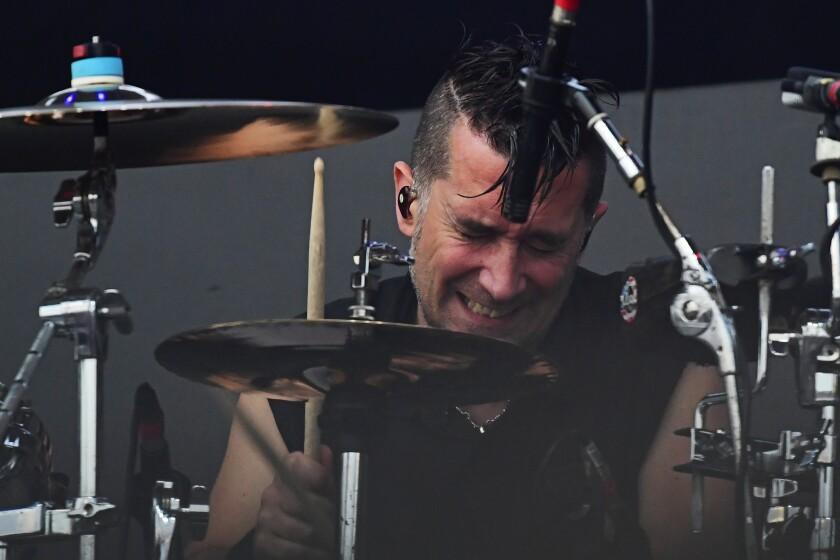 A man performs vigorously on a drum kit.