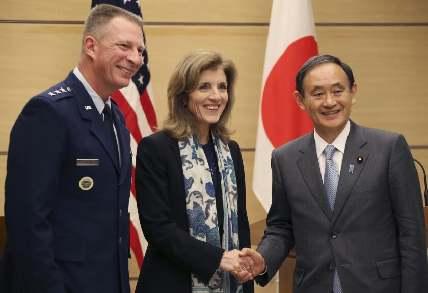 Japanese Chief Cabinet Secretary Yoshihide Suga, right, shakes hands with U.S. Ambassador to Japan Caroline Kennedy, center, as Lt. Gen. John Dolan, Commander of U.S. Forces Japan, smiles after their joint press conference at Japanese Prime Minister's official residence in Tokyo, Friday, Dec. 4, 20