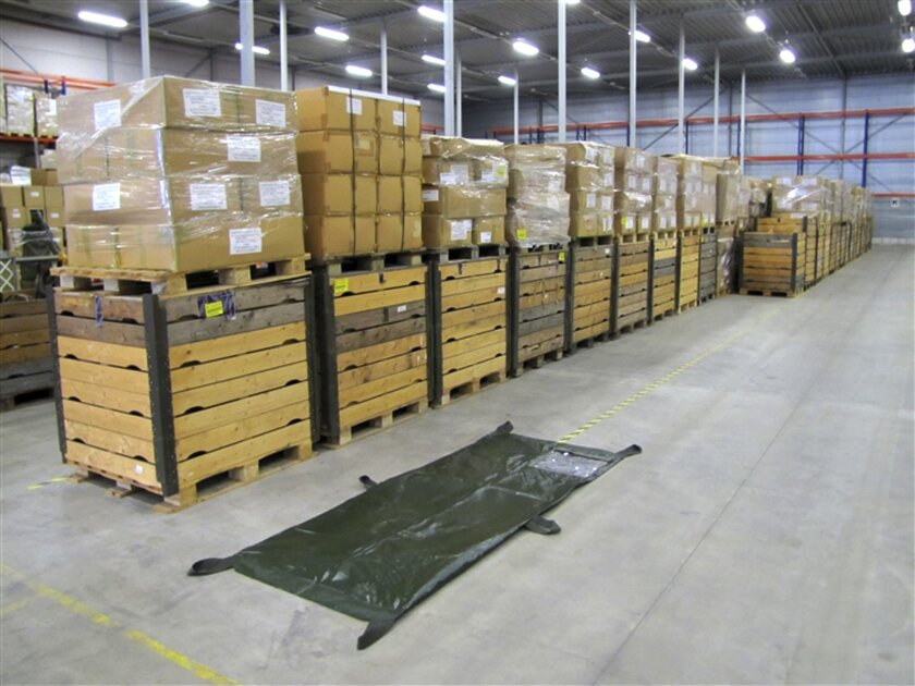 """In this undated but recent handout photo provided by BVA-Auctions.com, a body bag is displayed next to pallets containing about 2500 body bags put up for auction by the Dutch government Thursday, Oct. 2, 2014. Call it an offer to die for. The government is selling off 2,500 body bags in an online auction. Rob Meijer, commercial director of BVA Auctions, said Thursday his company sells plenty of strange stuff, but """"this is special."""" The bags are being sold in a single lot, which has a reserve price of 4,000 euros (usd 5,050). The auction closes on Oct. 6. (AP Photo/BVA-Auctions.com, HO)"""