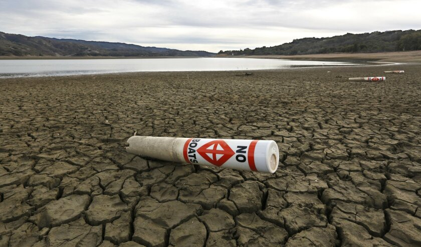 FILE -- In this Feb. 4, 2014 file photo a warning buoy sits on the dry, cracked bed of Lake Mendocino near Ukiah, Calif.  Gov. Jerry Brown was governor the last time California had a drought of epic proportions, in 1975-76 and now is pushing a controversial $25 billion plan to build twin tunnels to