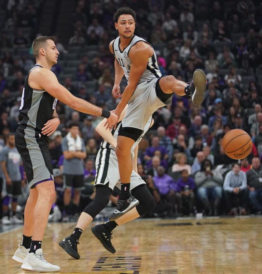 El jugador de los Sacramento Kings Nemanja Bjelica (i) pasa el balón entre las piernas de Bryn Forbes, de los San Antonio Spurs, durante un partido de la NBA. EFE/Archivo ]