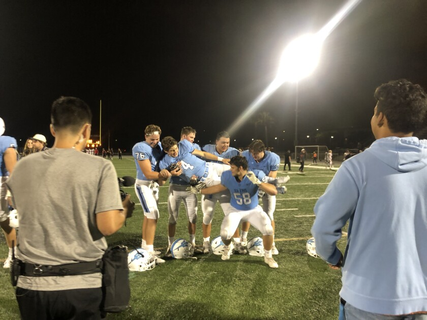 Quarterback Ethan Garbers of Corona del Mar poses with his offensive line after 42-21 win over San Clemente.