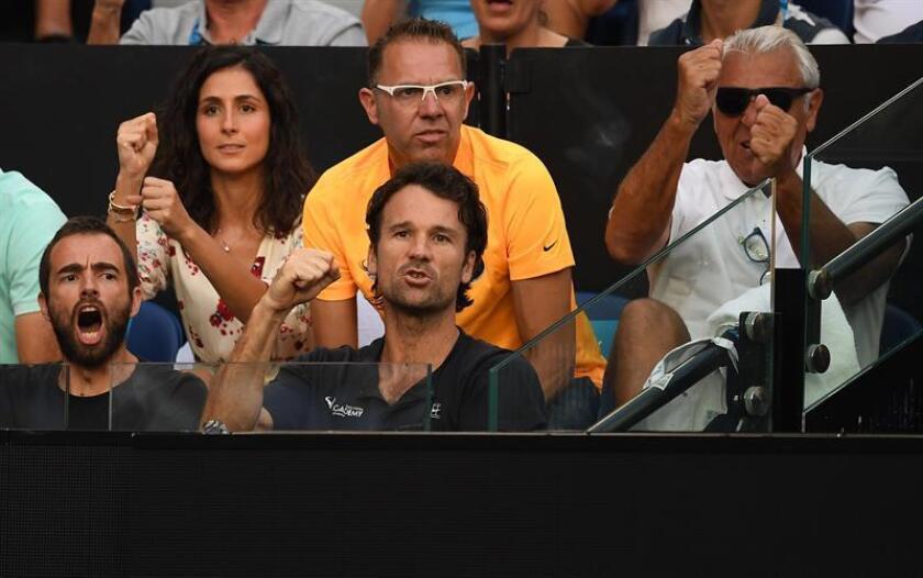 La novia del tenista español Rafael Nadal, Xisca Perelló (i), y su entrenador, Carlos Moyá (c), siguen desde las gradas la semifinal masculina del Abierto de Australia que disputaron Nadal y el griego Stefanos Tsitsipas, en Melbourne, Australia. EFE