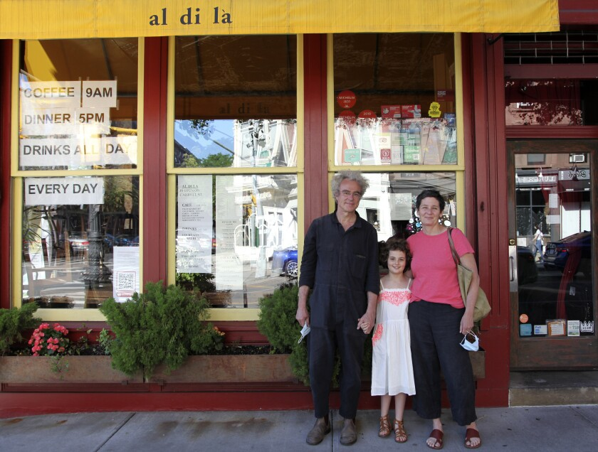 In this June 14, 2020 photo, Emiliano Coppa, left, and chef Anna Klinger pose with their daughter outside their trattoria, Al di La, in the Park Slope neighborhood in the Brooklyn borough of New York. The coronavirus has decimated the restaurant industry, leaving millions unemployed and shuttering spots for good. Many dine-in restaurants have turned to delivery or takeout, like Al di La. (Lisa Tolin via AP)