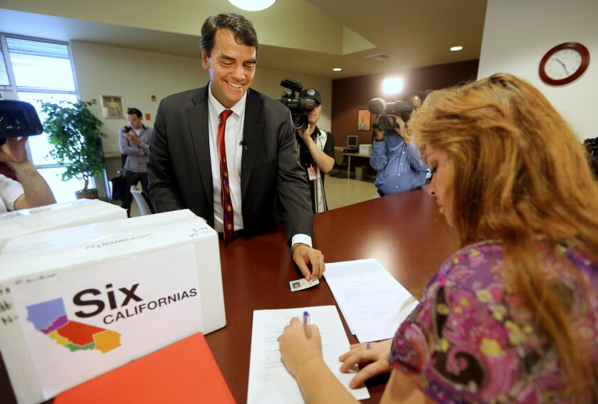 Silicon Valley venture capitalist Tim Draper presents his driver's license to Heather Ditty, elections manager for the Sacramento County Registrar of Voters, as he turns in boxes of petitions for a ballot initiative that would ask voters to split California into six separate states.