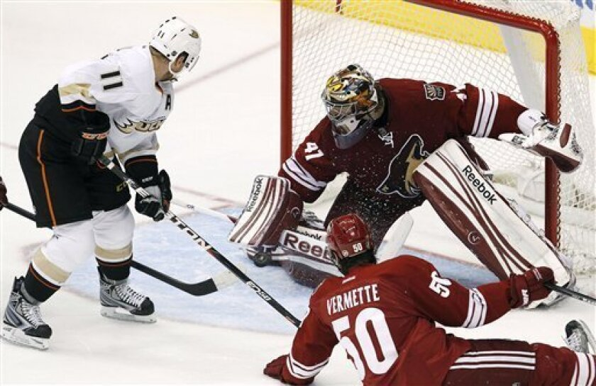 Phoenix Coyotes goalie Mike Smith (41) makes a save on a shot by Anaheim Ducks' Saku Koivu (11), of Finland, as Coyotes' Antoine Vermette (50) slides in to defend during the second period in an NHL hockey game, Saturday, March 31, 2012, in Glendale, Ariz. (AP Photo/Ross D. Franklin)