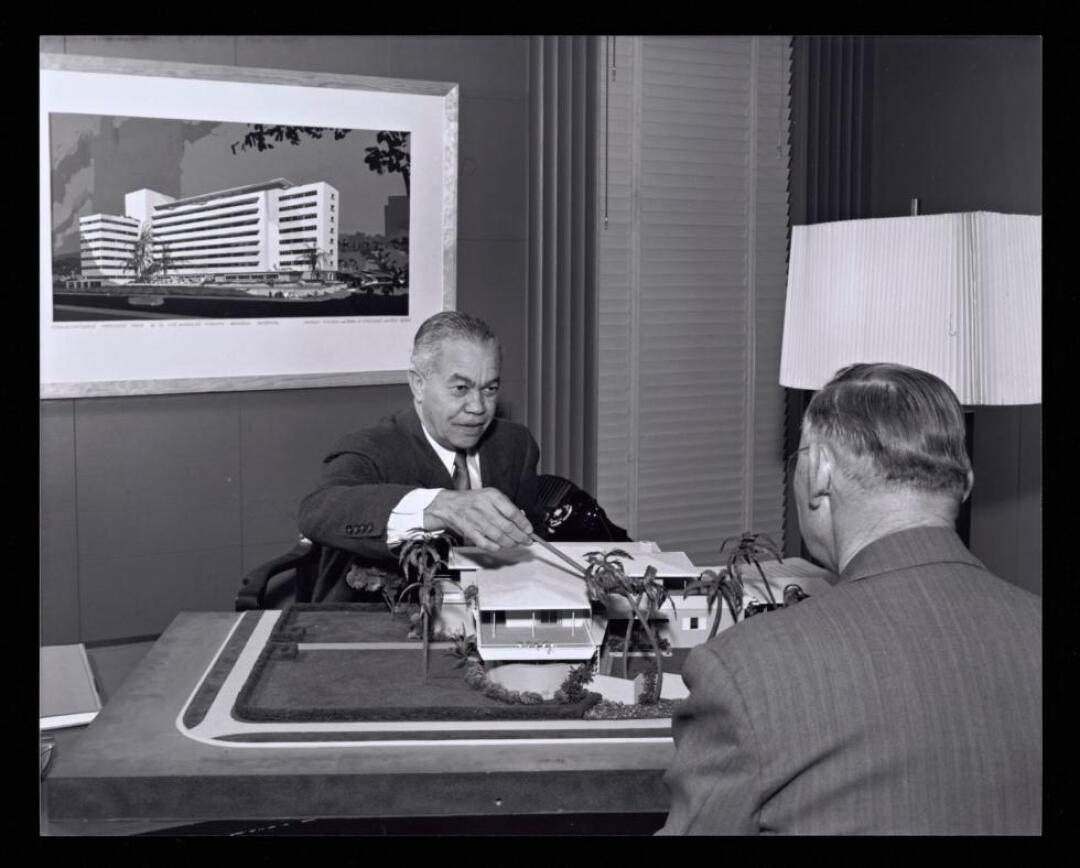 In a black-and-white image, architect Paul Williams points at a model while seated at his desk.