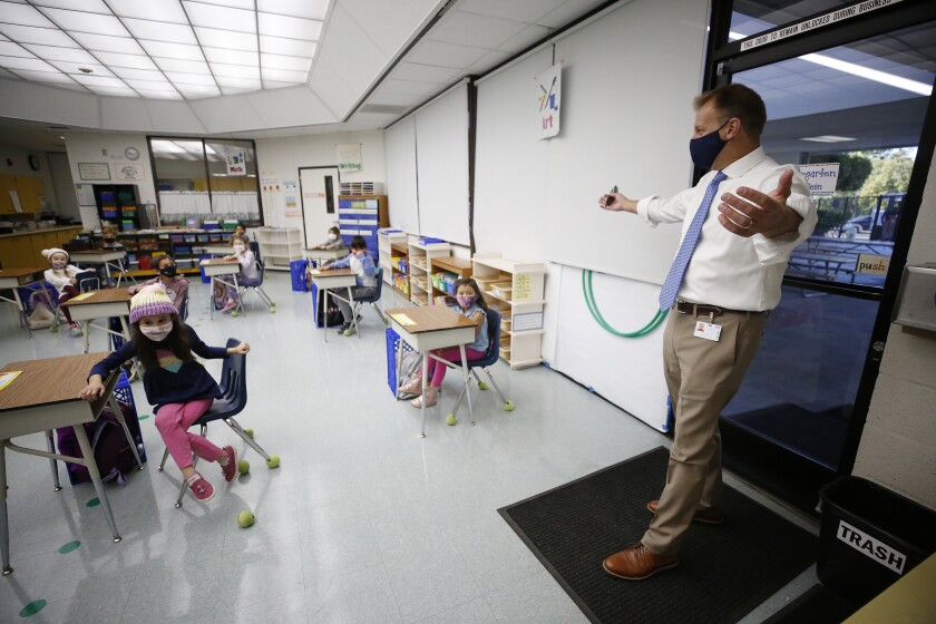 A school administrator stretches his arms out at the door of a classroom of young children at spaced-out desks