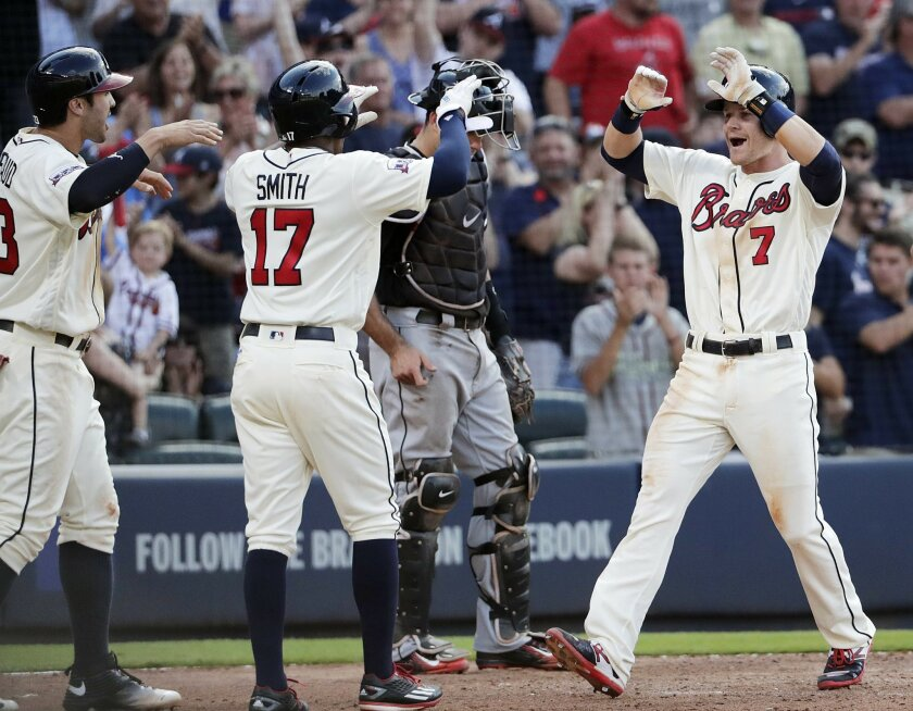 Atlanta Braves' Gordon Beckham, right, high-fives teammates Chase d'Arnaud, left, and Mallex Smith after they scored off Beckham's three-run home run in the seventh inning of a baseball game against the Miami Marlins, Saturday, May 28, 2016, in Atlanta. (AP Photo/David Goldman)