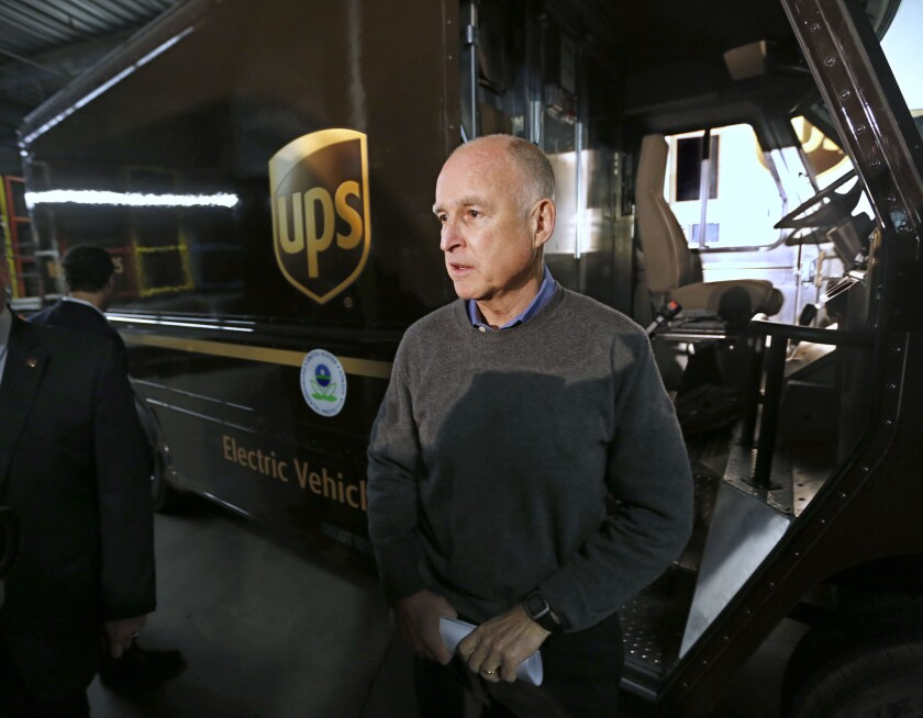 Gov. Jerry Brown talks to reporters after inspecting an electric-powered UPS delivery truck at the UPS distribution center in West Sacramento last month.