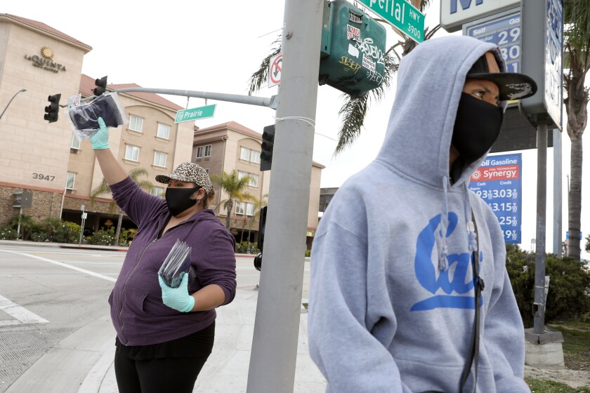 Brenda Mendez and son David Mendez sell masks on Prairie Avenue