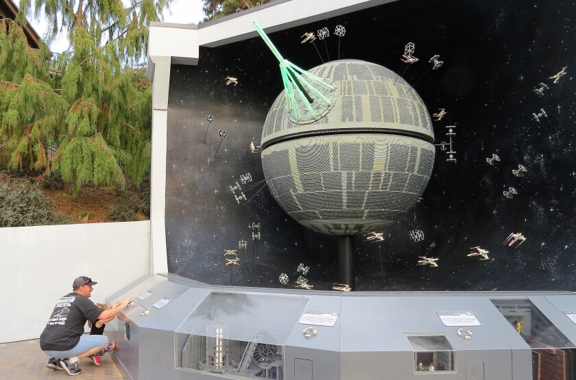 A father and daughter push automation buttons for the Death Star model, made from 500,000 Lego bricks, in the Star Wars Miniland attraction at Legoland California theme park in Carlsbad on Nov. 18. The Star Wars attraction will close for good on Jan. 6.