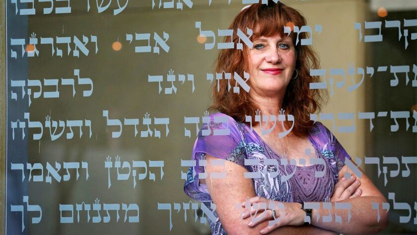Cheri Weiss, a cantorial intern at Congregation Beth El in La Jolla, looks through scripture found on the glass walls of the synagogue.