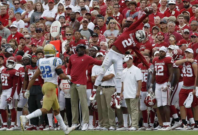 Oklahoma receiver CeeDee Lamb makes a spectacular catch but can't stay in bounds against Bruins cornerback Nate Meadors in the third quarter of their game.