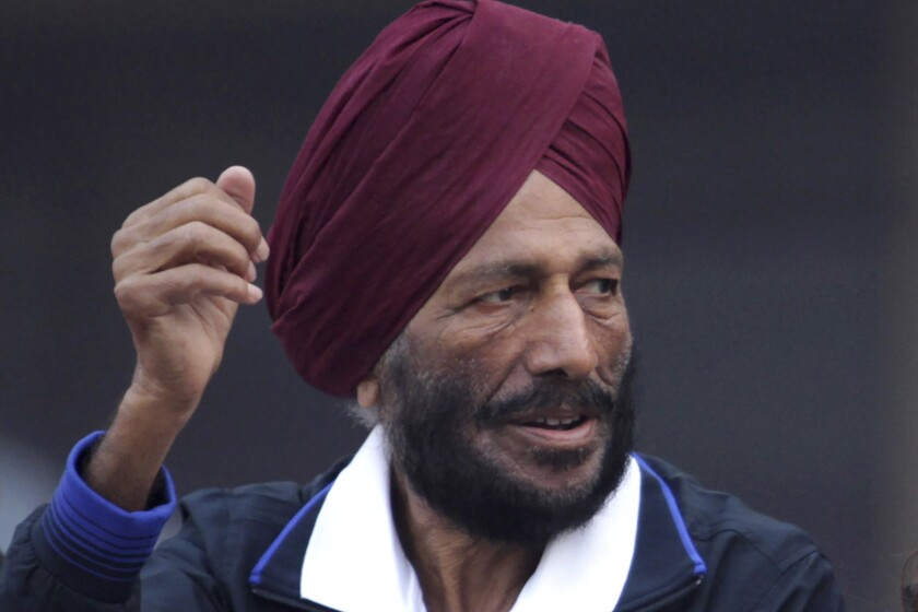 FILE - In this Dec. 15, 2013, file photo, former Indian athlete Milkha Singh, with, and Bollywood actor Bipasha Basu waves to the participants during the Delhi Half Marathon in New Delhi, India. Milkha Singh, one of India's first sport superstars and ace sprinter who overcame fought a childhood tragedy and became the country's most celebrated athlete, has died. He was 91.(AP Photo/Tsering Topgyal, File)