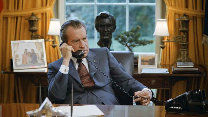 June 23, 1972. President Nixon seated at his desk, family photos and the Lincoln bust statuette are