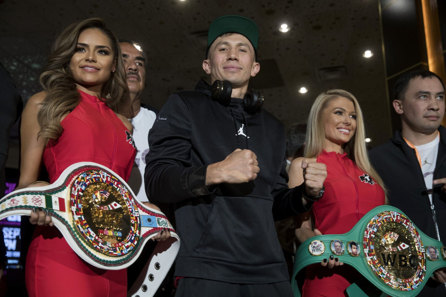 WBC/WBA middleweight champion Gennady Golovkin, center, of Kazakhstan poses in the lobby of the MGM Grand hotel-casino in Las Vegas Tuesday, Sept. 11, 2018. Golovkin will defend his titles against Canelo Alvarez of Mexico in a rematch at T-Mobile Arena in Las Vegas on Sept. 15. (Steve Marcus/Las Vegas Sun via AP)