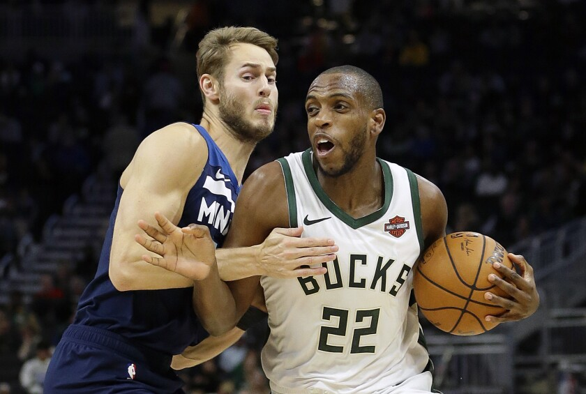 FILE - In this Oct. 17, 2019, file photo, Milwaukee Bucks' Khris Middleton (22) drives to the basket against Minnesota Timberwolves' Jake Layman during the first half of a preseason NBA basketball game in Milwaukee. Middleton is expected to be sidelined for up to a month after suffering a left thigh contusion. (AP Photo/Aaron Gash, File)