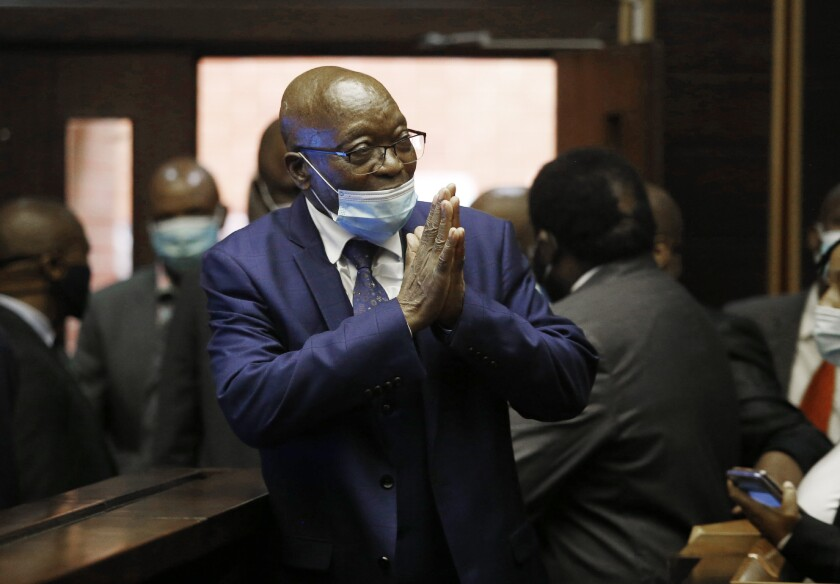 Former South African President Jacob Zuma, greets supporters on his arrival in the High Court in Pietermaritburg, South Africa, Monday, May 17, 2021. Zuma and French arms company Thales face corruption, racketeering and money laundering charges linked to an arms deal. (AP Photo/Rogan Ward/Pool)
