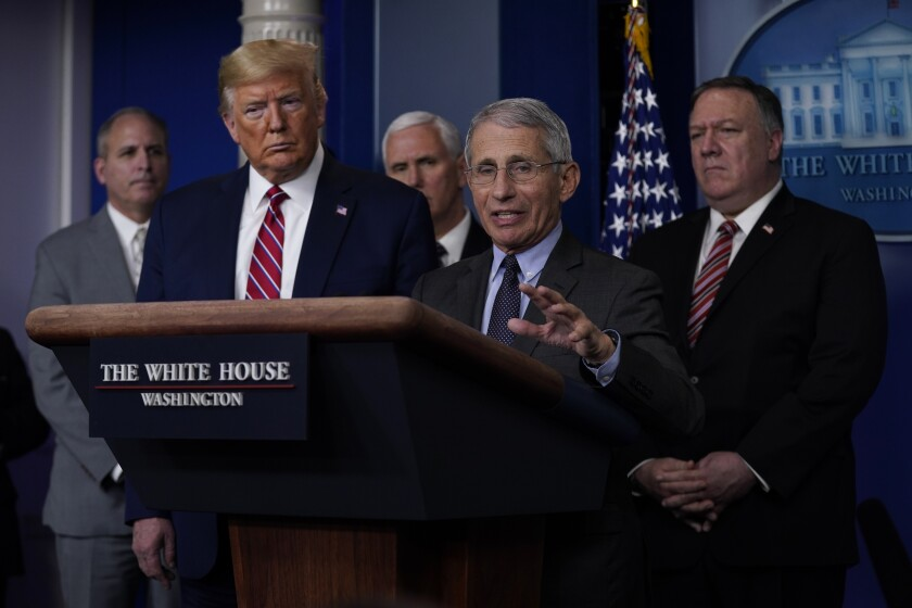Dr. Anthony Fauci speaks surrounded by President Trump and others at the White House.
