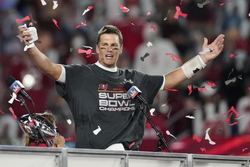 Tampa Bay Buccaneers quarterback Tom Brady raises his hands amid confetti.