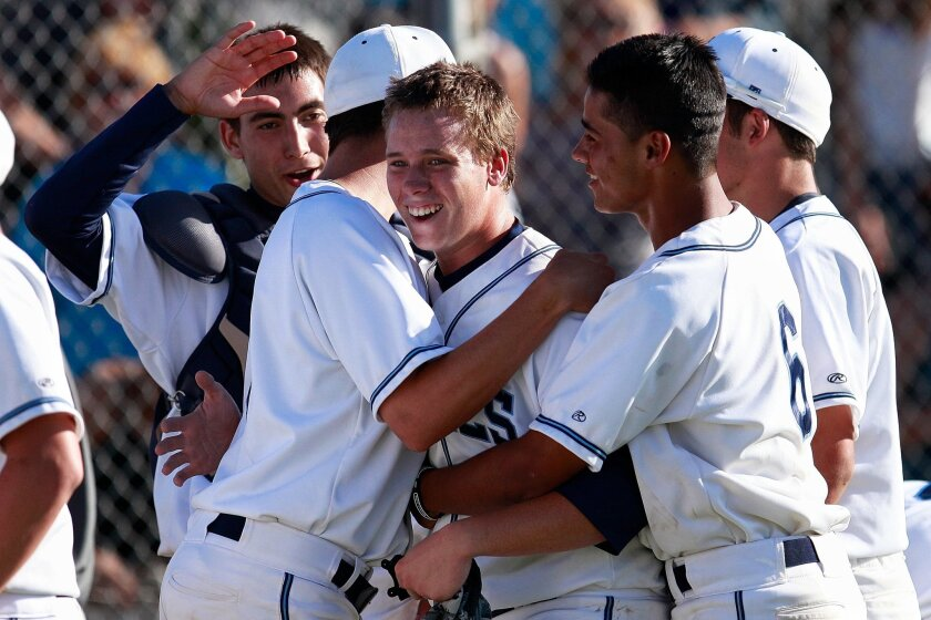 Granite Hills sophomore Dillan Shrum (center) is mobbed by teammates after his home run in the bottom of the eighth inning boosted the Eagles to a 3-2 Open Division playoff win over Cathedral Catholic.