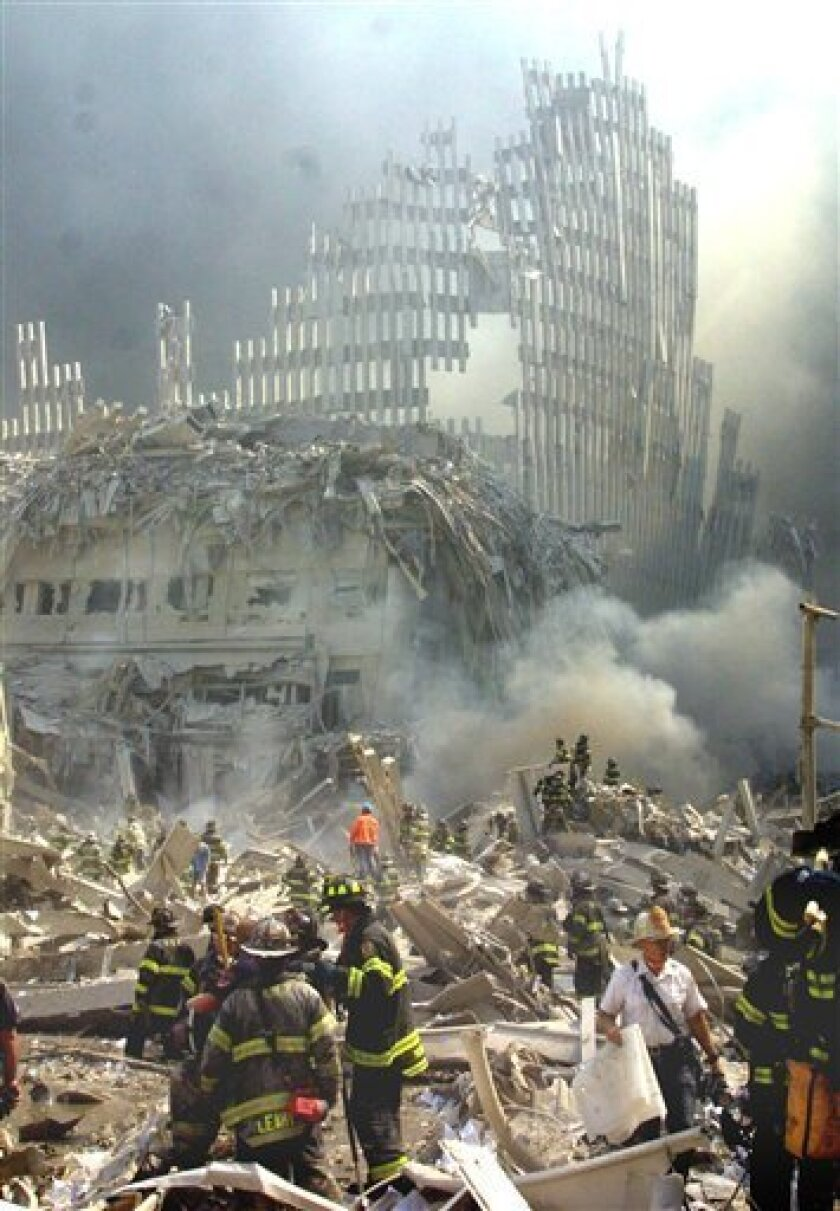 FILE- In this Sept. 11, 2001 file photo, a shell of what was once part of the facade of one of the twin towers of New York's World Trade Center rises above the rubble that remains after both towers were destroyed in the terrorist attacks. New York City has agreed to pay up to $657 million to settle more than 10,000 lawsuits filed by ground zero rescue and response workers who say they were sickened by World Trade Center dust. (AP Photo/Shawn Baldwin, File)
