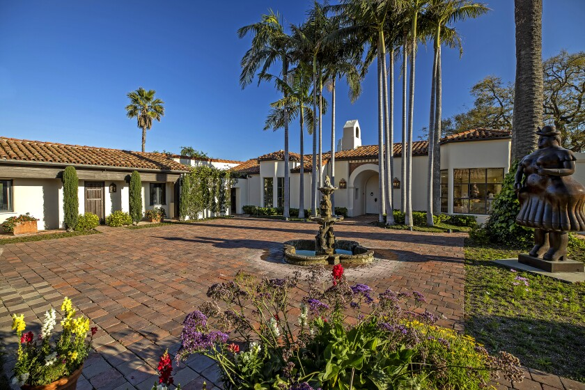 The large flagstone courtyard of the Mediterranean-style mansion includes a fountain.