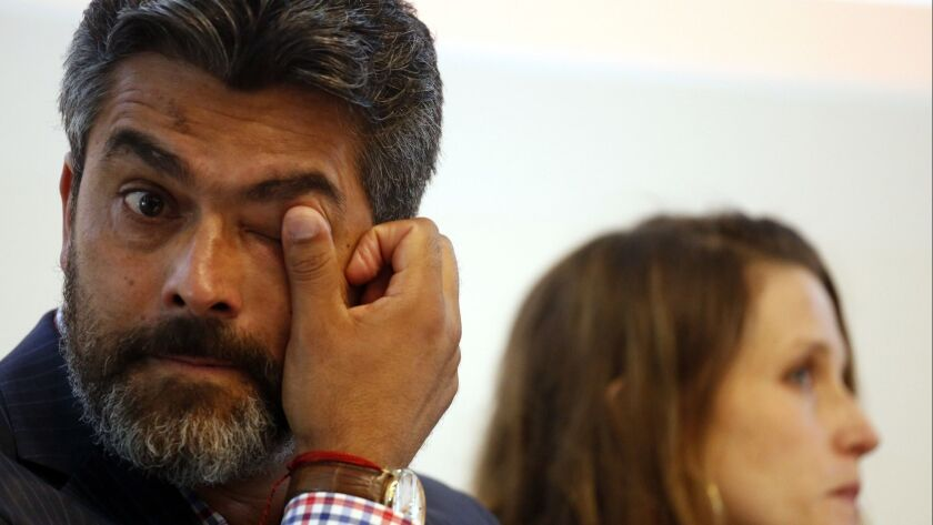 "Francisco ""Franky"" Carrillo, Jr., who was wrongfully imprisoned for 20 years, seated next to his wife Efty Sharony, wipes a tear from his eye on August 4, 2016."