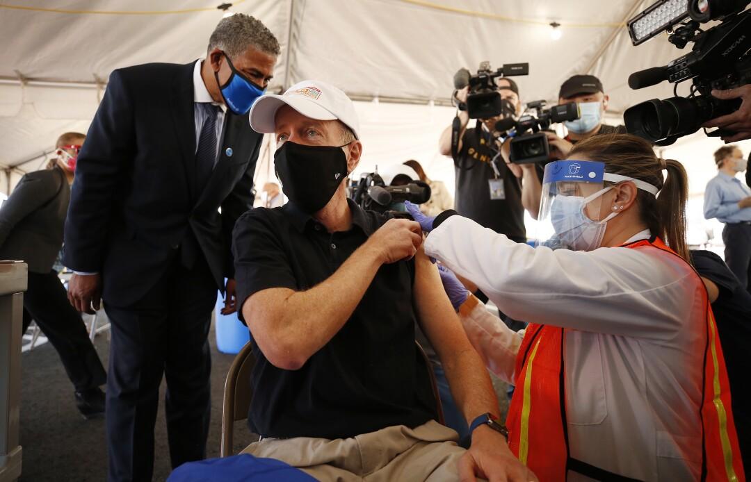 Austin Beutner receives a shot inside a tent.
