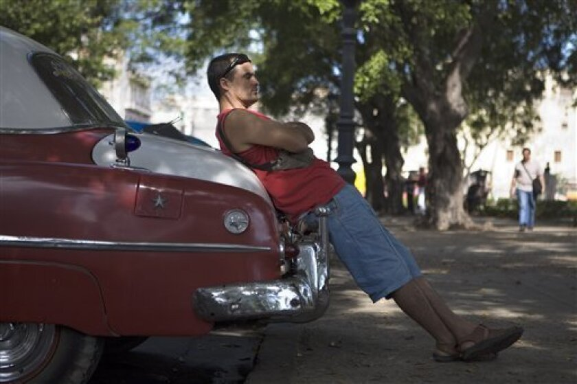 Taxi driver Jordan Marero leans on the back of his 1952 Pontiac Catalina as he waits for passengers in Havana, Monday, Jan. 12, 2009. Cuban officials said they are ending a nearly decade-long ban on new licenses for private taxis and they will even let cabbies set their own fares. (AP Photo/Dario L