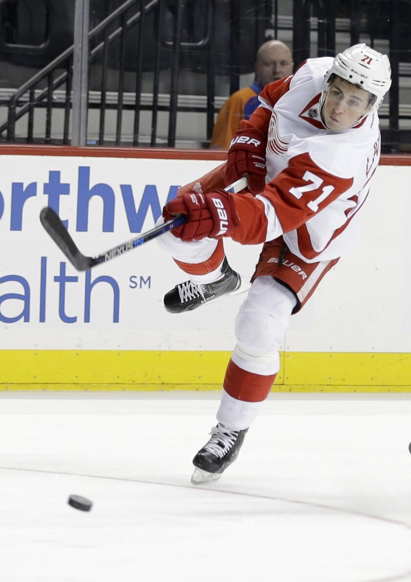 Detroit Red Wings' Dylan Larkin takes a shot during the first period of an NHL hockey game against the New York Islanders, Monday, Feb. 15, 2016, in New York. (AP Photo/Seth Wenig)