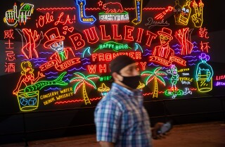 LOS ANGELES, CA - MAY 21: Malachi Stewart walks finishes taking pictures of the neon wall on the S. Hill Street side of Grand Central Market, in downtown Los Angeles, CA, as food halls, food courts, large and small are re-opening under CDC guidelines, photographed Thursday, May 21, 2020, during the coronavirus pandemic. A resident of South Central L.A. his whole life, Stewart says he has made a few trips to the Market for favorites like tacos, since the Safer at Home orders went into effect. (Jay L. Clendenin / Los Angeles Times)
