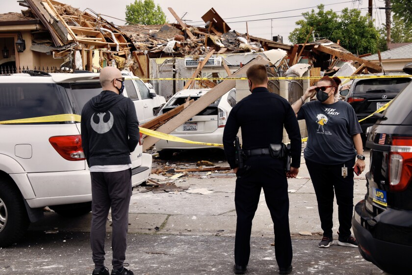 Two people speak to a police officer in front of a destroyed garage