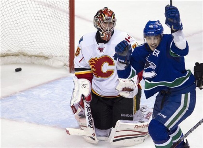 Calgary Flames goalie Henrik Karlsson (35) looks on as Vancouver Canucks center Maxim Lapierre (40) celebrates teammate Vancouver Canucks defenseman Marc-Andre Gragnani's, not shown,  goal during third period NHL hockey action at Rogers Arena in Vancouver, British Columbia, Saturday, March, 31, 201