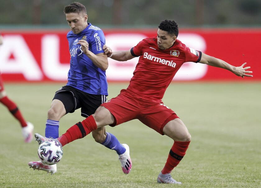 FILE - In this Tuesday, June 9, 2020 file photo, Saarbruecken's Mario Mueller, left, and Leverkusen's Paulinho challenge for the ball during the German soccer cup, DFB Pokal, semifinal match between 1. FC Saarbruecken and Bayer 04 Leverkusen in Voelklingen, Germany. Bayer Leverkusen will be without Brazilian forward Paulinho for the German Cup final and the Europa League mini-tournament after he tore an anterior cruciate ligament in his knee, the club said Thursday July 2, 2020. (Ronald Wittek/Pool Photo via AP)