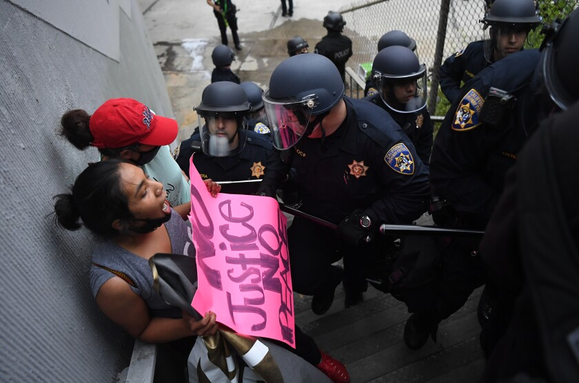 Protesters are escorted off the northbound 110 Freeway in downtown Los Angeles on Friday.