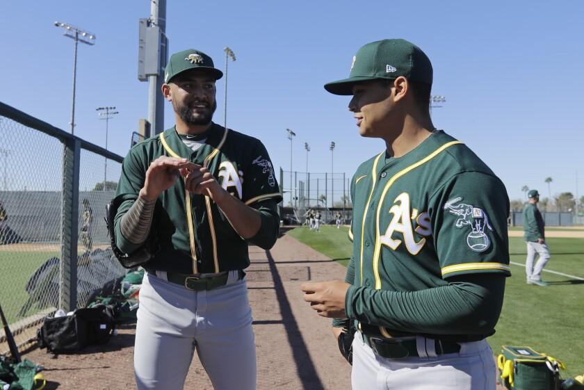 The Athletics' Sean Manaea, left, talks with Jesus Luzardo during spring training baseball practice, Thursday, Feb. 13, 2020, in Mesa, Ariz.