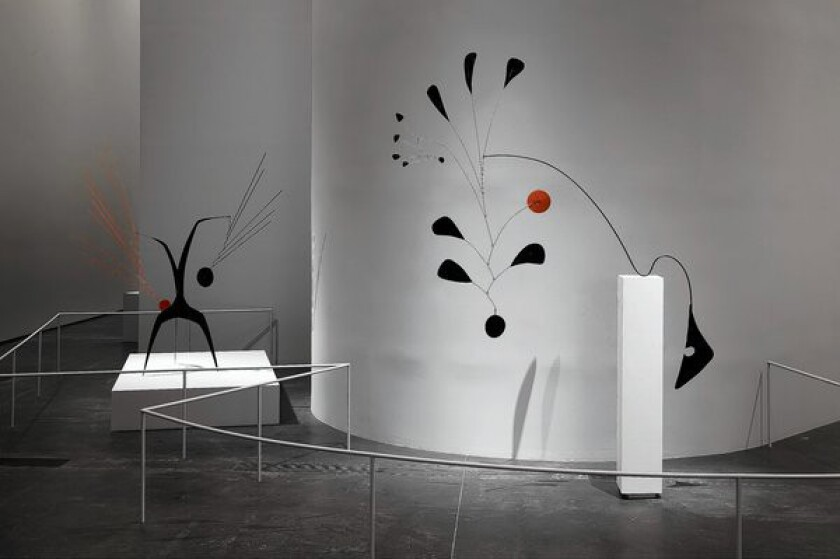 Abstract red and black metal sculptures in a museum in front of white walls