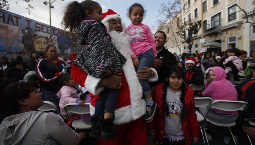 Santa (Jorge Grajeda of Pomona) carries Angelica Romero, 4, left, of Hawaiian Gardens and Maya Epps, 5, of Pomona as he leads a crowd to the toy giveaway at Fred Jordan Mission in Los Angeles in 2013.