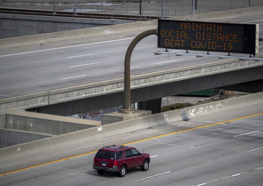 A sign reminds motorists traveling on the 105 Freeway in El Segundo to practice social distancing.