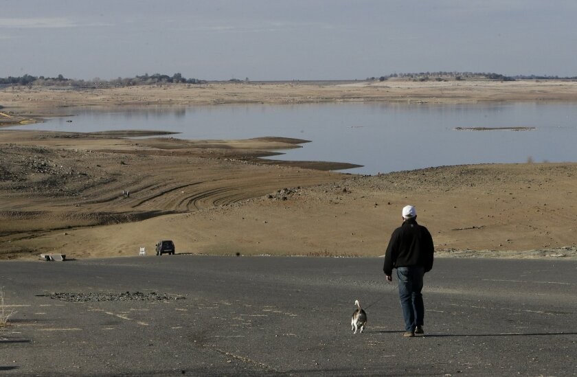 FILE - In this Jan. 9, 2014 file photo, a visitor to Folsom Lake, Calif.,  walks his dog down a boat ramp that is now several hundred yards away from the waters' edge. Gov. Jerry Brown formally proclaimed California in a drought Friday Jan. 17, 2014, saying the state is in the midst of perhaps its