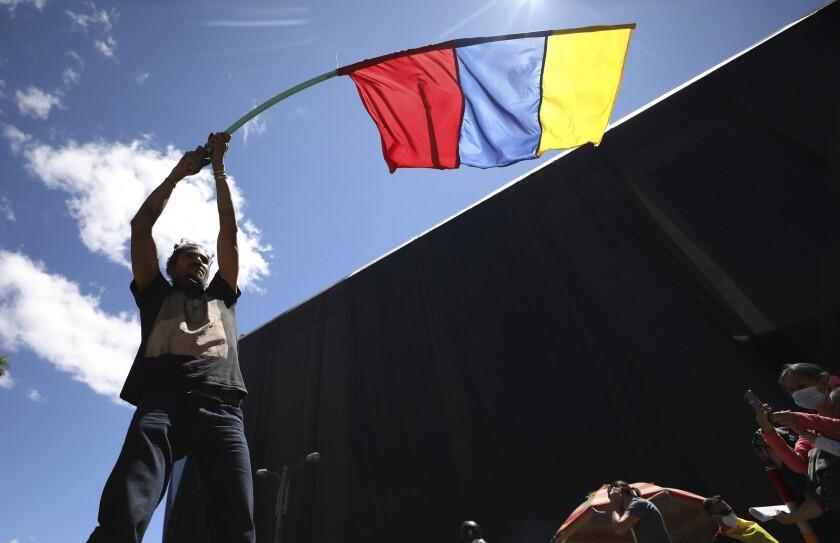 Un hombre ondea una bandera de Colombia el miércoles 2 de junio de 2021 durante una manifestación antigubernamental, la cual fue desatada por una propuesta de incremento fiscal a los servicios públicos, el combustible, los salarios y las pensiones, en Bogotá, Colombia. (AP Foto/Fernando Vergara)